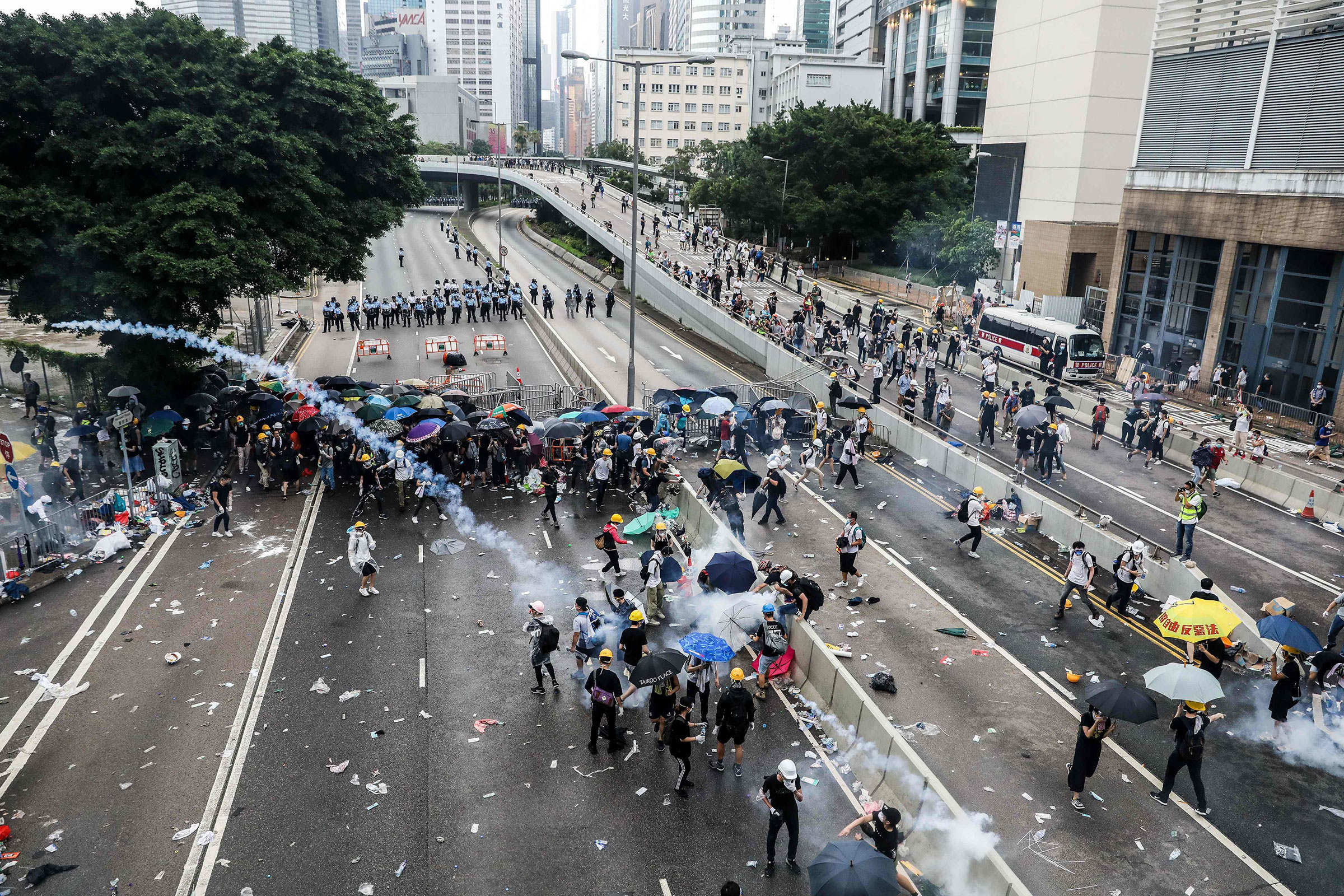 Protesters throw back a tear gas canister fired by police during a rally against an extradition law proposal outside the government headquarters in Hong Kong on June 12.