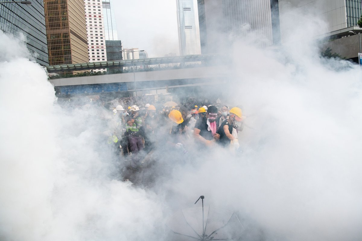 Protesters walk through a cloud of tear gas on June 12.