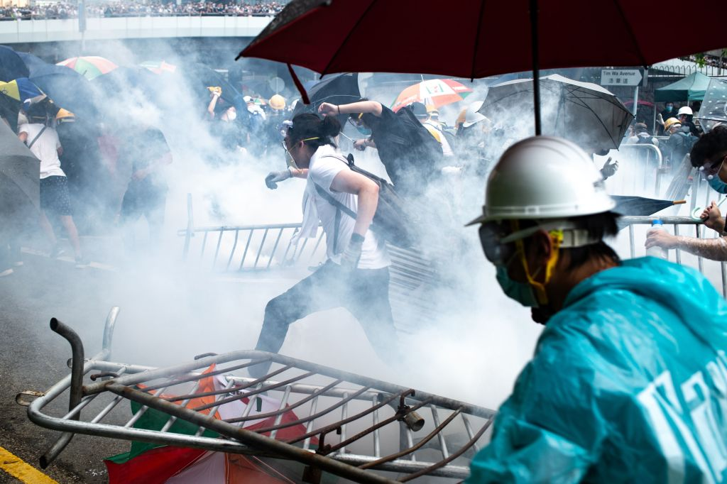 Protesters run after police fired tear gas during a rally against a controversial extradition law proposal outside the government headquarters in Hong Kong on June 12, 2019.