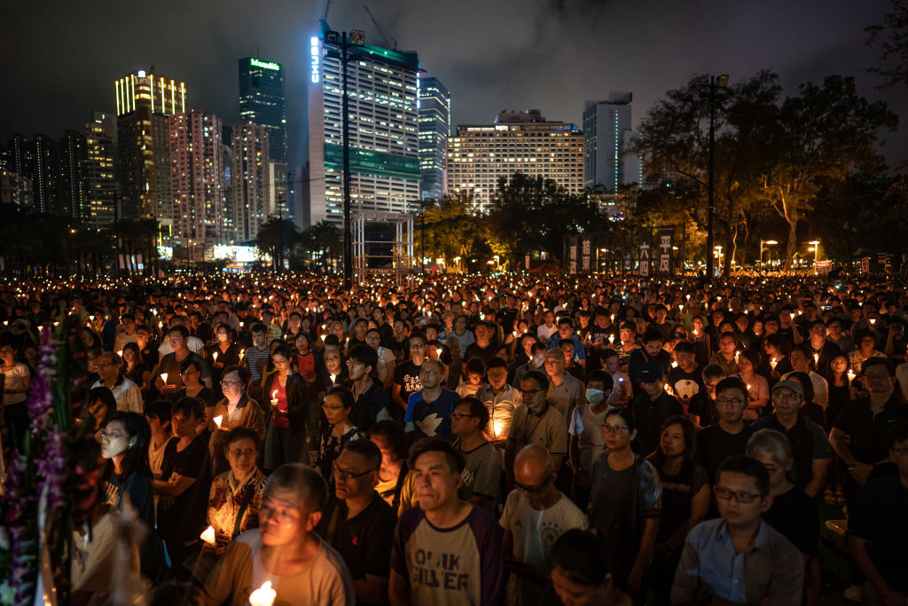 People hold candles as they take part in a candlelight vigil at Victoria Park in Hong Kong on on June 4, 2019.