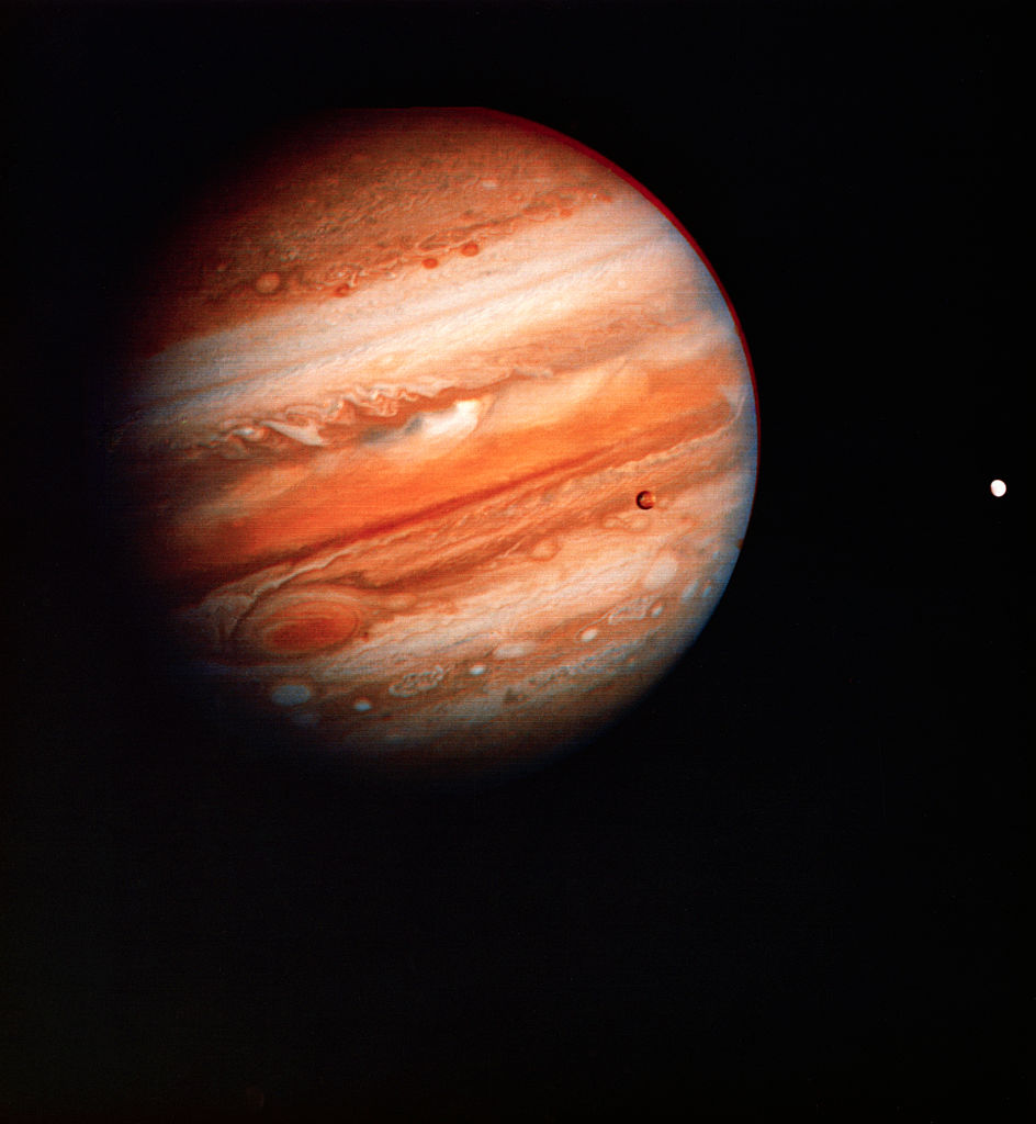An view of Jupiter from early in the Voyager 1 mission. The two Galilean moons of Io and Europa (left to right) can also be seen.