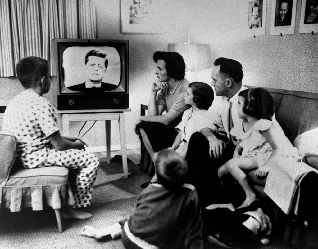 Typical American family gathered around TV, which displays John F. Kennedy's face, to watch debate between Kennedy & Richard Nixon during presidential election.