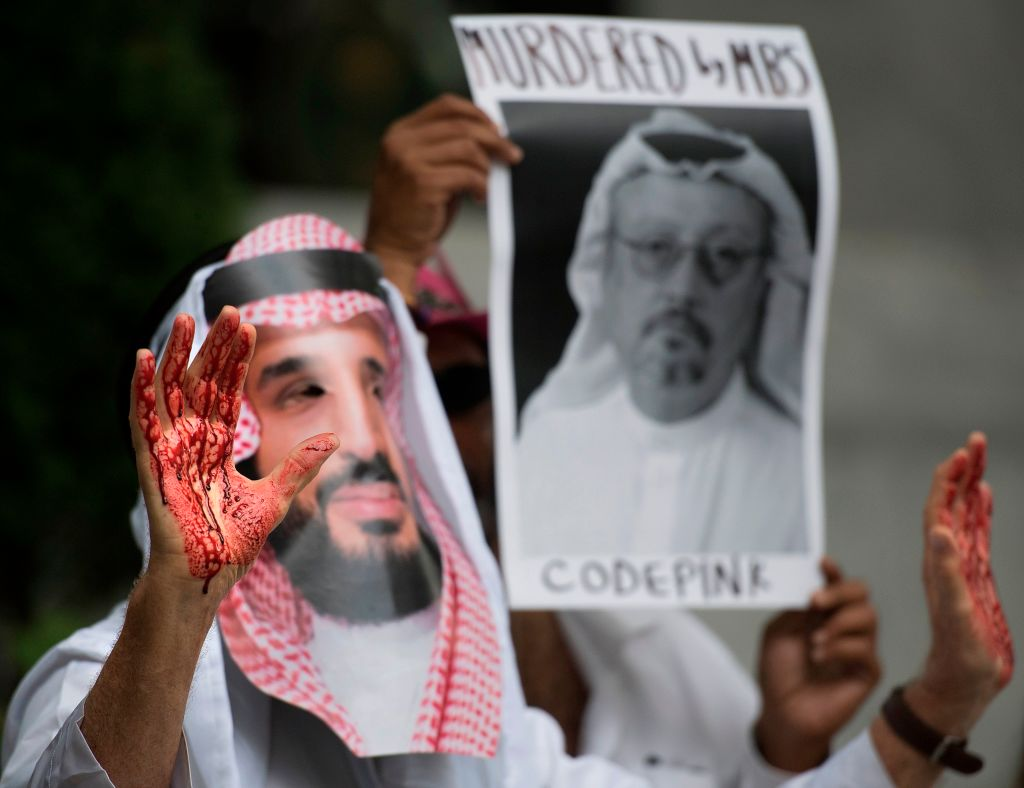 A demonstrator dressed as Saudi Arabian Crown Prince Mohammed bin Salman (C) with blood on his hands protests outside the Saudi Embassy in Washington, DC, on Oct. 8, 2018.