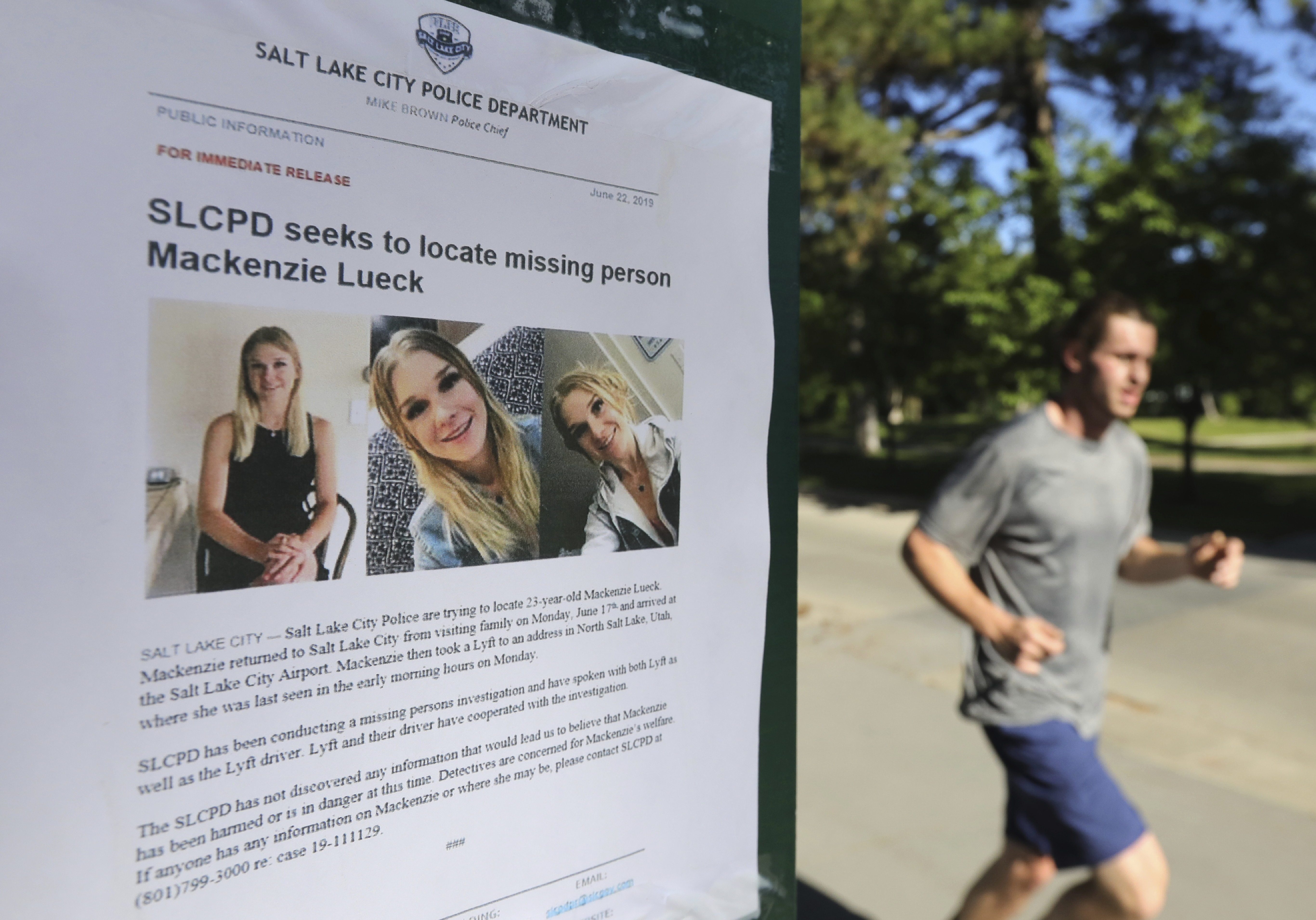 In this June 24, 2019 file photo, a jogger runs pass a poster of Mackenzie Lueck at Liberty Park in Salt Lake City. One person was taken into custody Friday, June 28, in connection with the disappearance of Lueck, a Utah college student who disappeared 11 days ago.