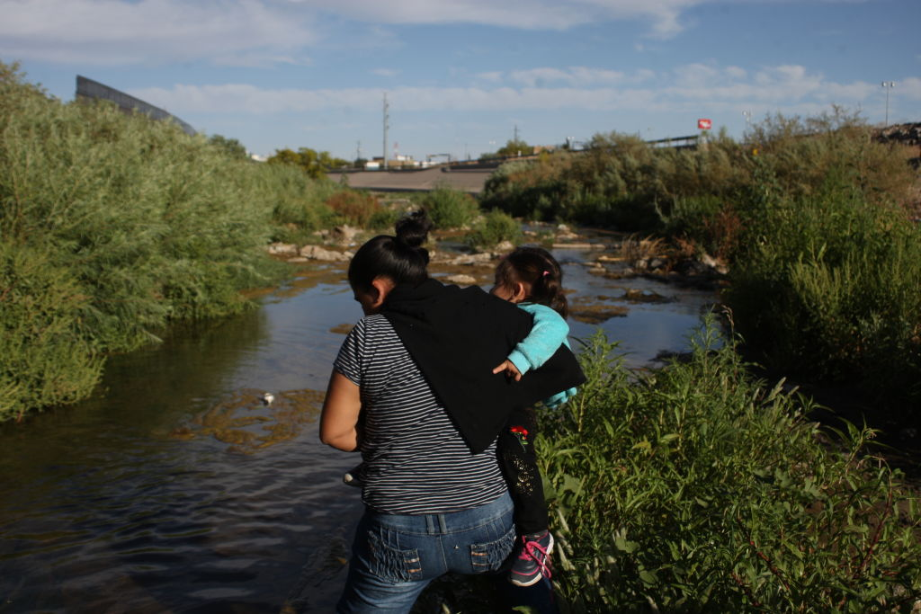 A woman crosses the Rio Bravo, Mexico, with her son in her arms, to reach the United States surrender to border patrol agents and request asylum, on May 19, 2019.