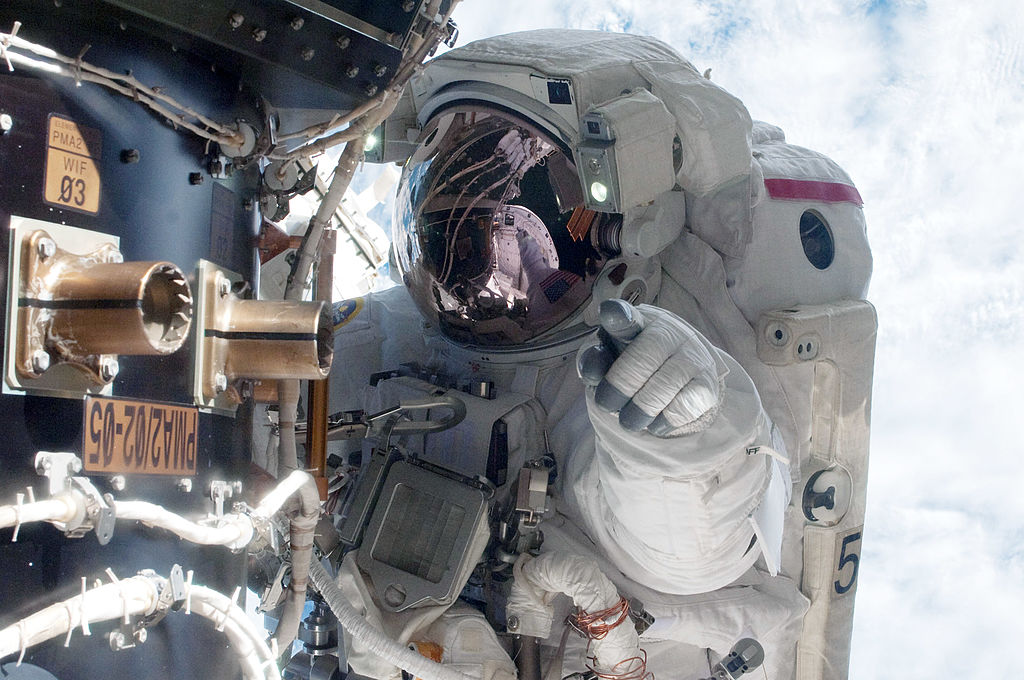 In this handout image provided by the National Aeronautics and Space Administration (NASA), NASA astronaut Mike Fossum, Expedition 28 flight engineer, waits at an International Space Station's pressurized mating adapter (PMA-2) docked to the space shuttle Atlantis, as the station's robotic system moves the failed pump module (out of frame) over to the spacewalking astronaut and the shuttle's cargo bay during a planned six-and-a-half-hour spacewalk July 12, 2011 in space.