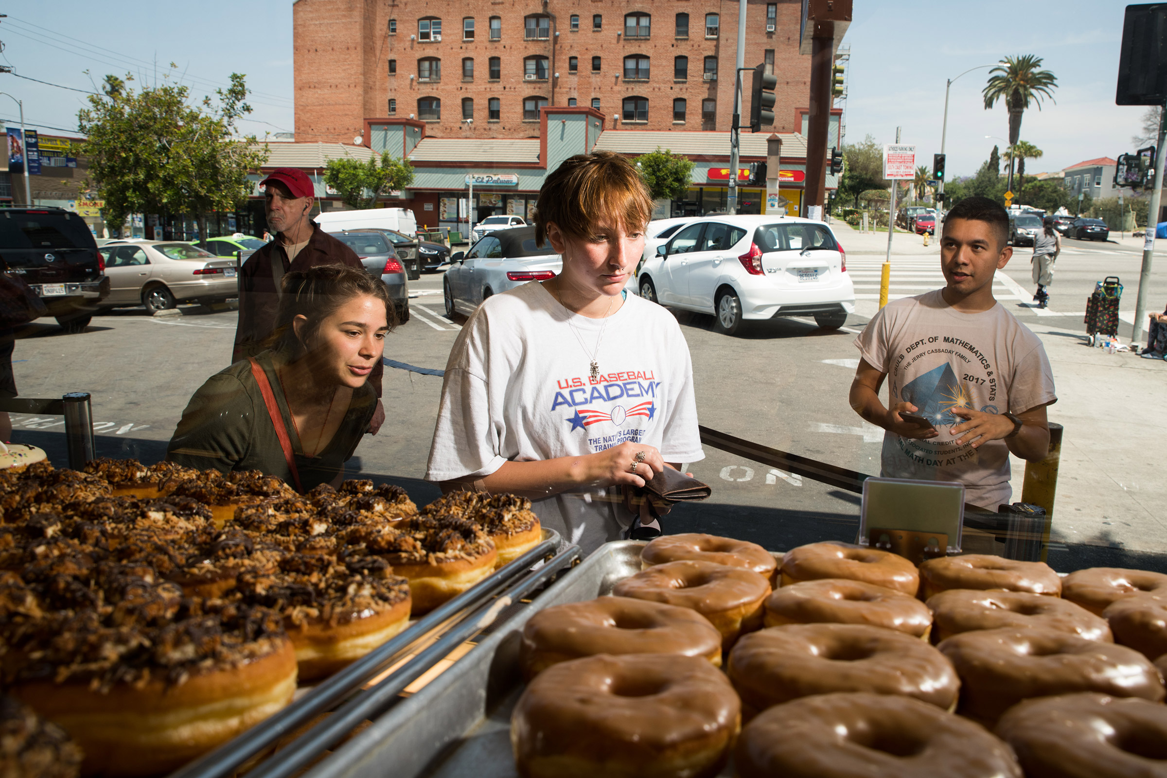 Katy McAfee, left, Abigail Logan, center, and Matthew Ortega pick out doughnuts at California Donuts in Los Angeles on June 6, 2019.
