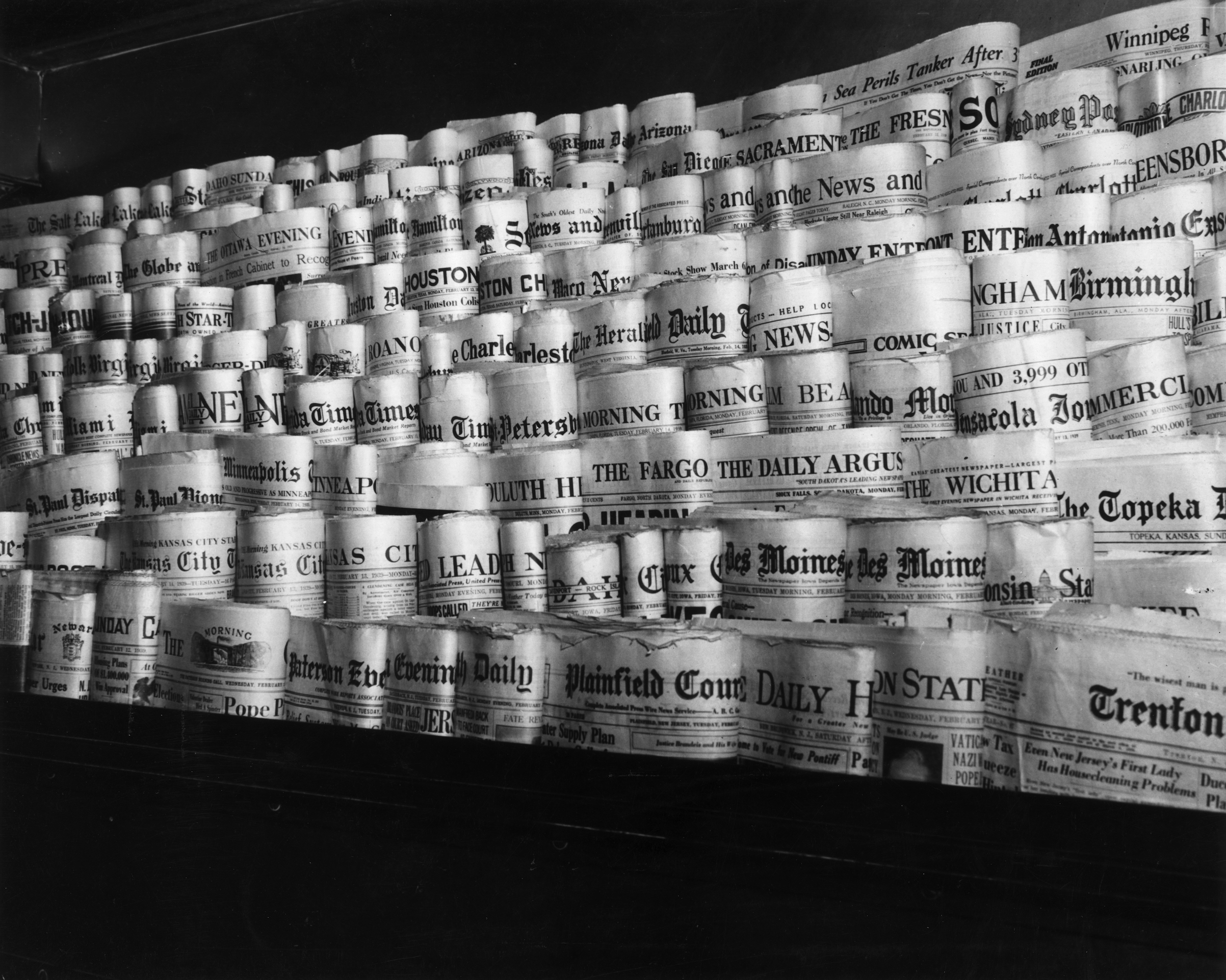 February 1939:  View of rows of newspapers from various American cities sitting in the racks of a newsstand, Times Square, New York City.