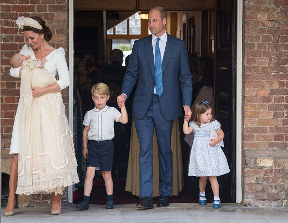 Princess Charlotte of Cambridge and Prince George of Cambridge hold hands with their father, Prince William, Duke of Cambridge, as Prince Louis of Cambridge is carried by his mother, Catherine, Duchess of Cambridge after his christening service at the Chapel Royal, St James's Palace, London on July 9, 2018.