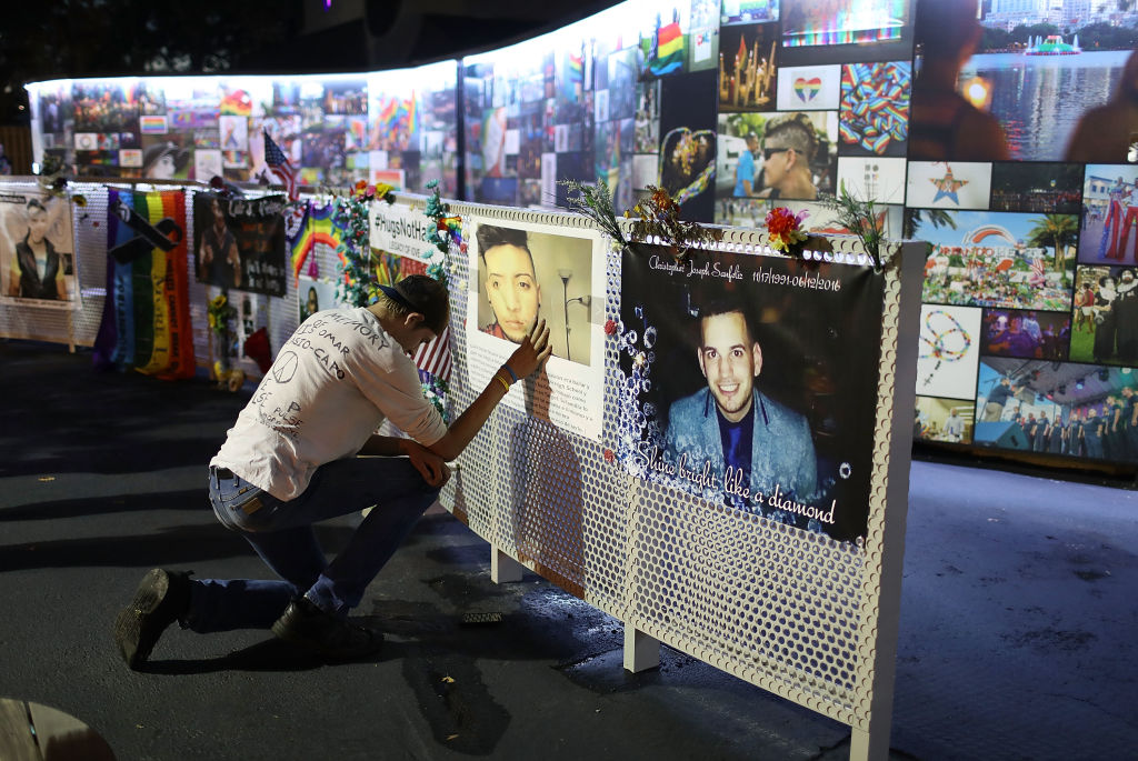 William True spends a moment in front of a picture of his friend Luis Omar Ocasio-Capo at the memorial to the 49 shooting victims setup at the Pulse nightclub on June 11, 2018 in Orlando, Florida. On June 12, 2016 a mass shooting took place at the Pulse nightclub killed 49 people and wounded 53.