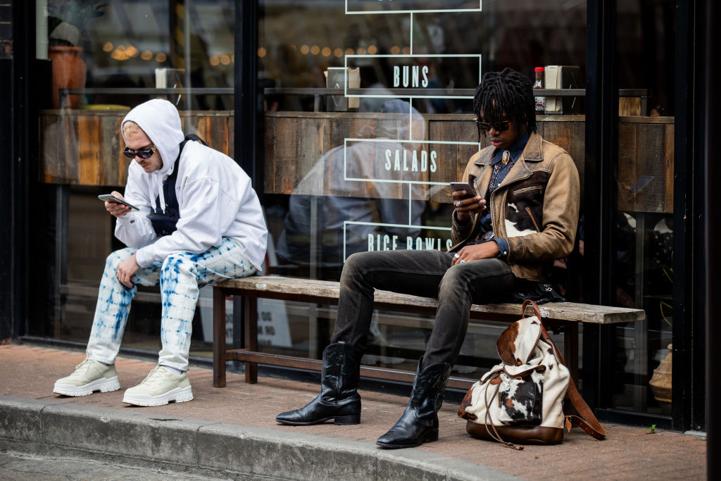 Guests sitting on a bench texting seen outside Iceberg during London Fashion Week Men's June 2019 on June 08, 2019 in London, England.