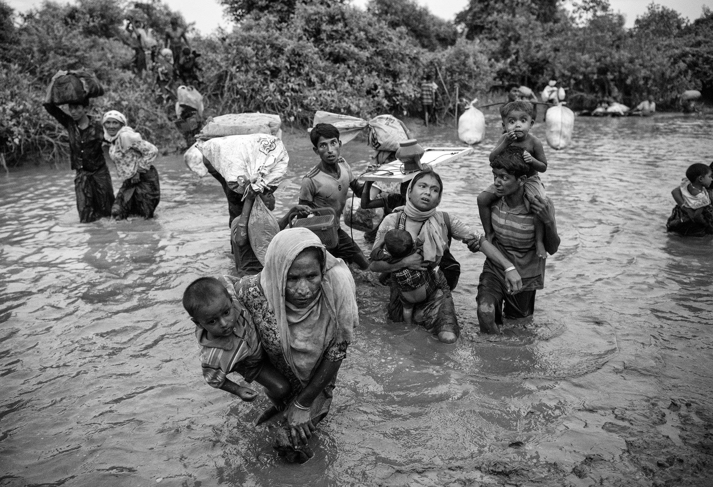 Rohingya Muslim refugees cross a canal as they flee over the border from Myanmar into Bangladesh at the Naf River on Nov. 1, 2017 near Anjuman Para in Cox's Bazar, Bangladesh.