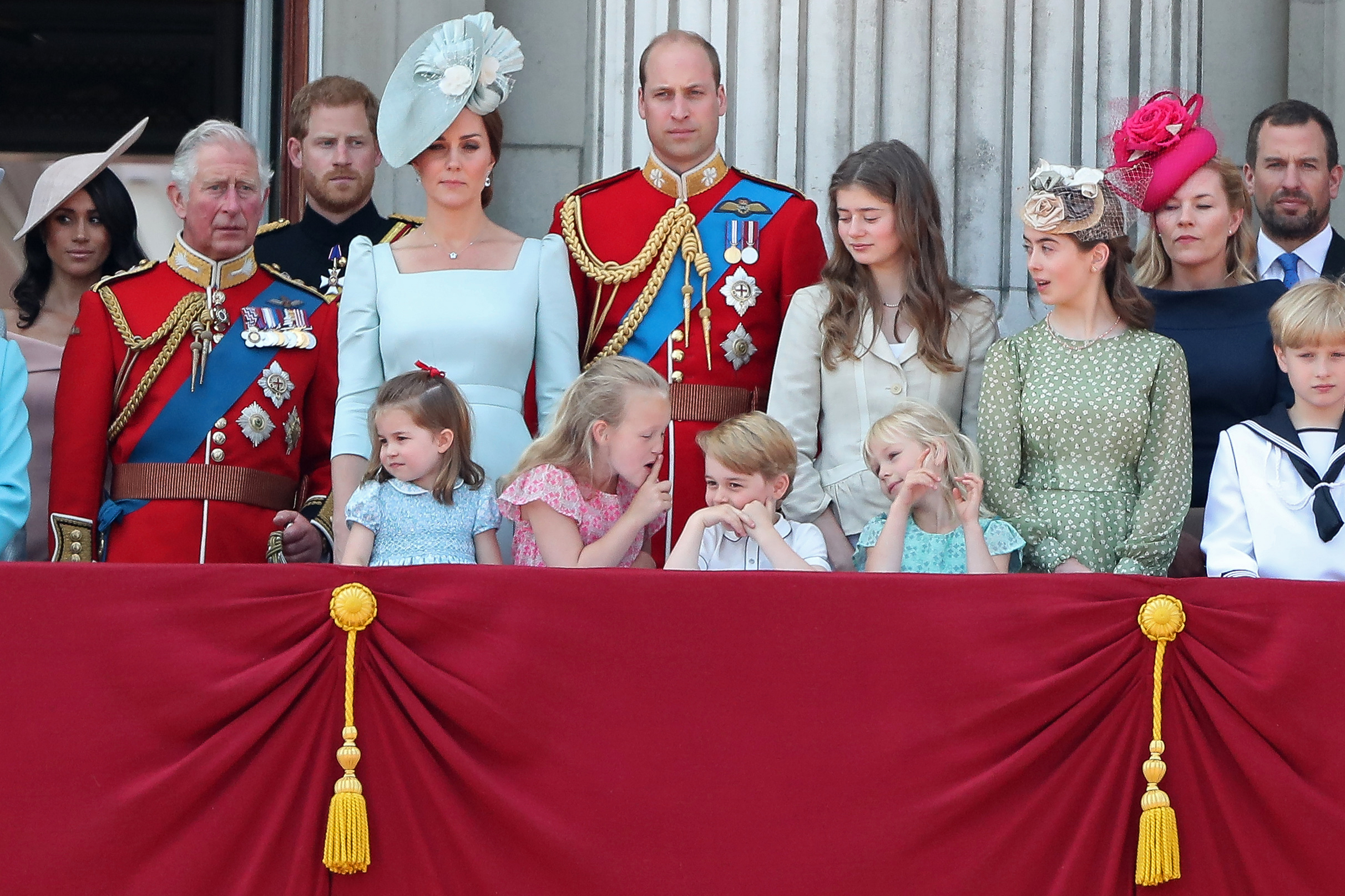 In the front row (L-R), children, Princess Charlotte of Cambridge, Savannah Phillips, Prince George of Cambridge and Isla Phillips chat on the balcony of Buckingham Palace as members of the Royal Family gather to watch a fly-past of aircraft by the Royal Air Force, in London on June 9, 2018.