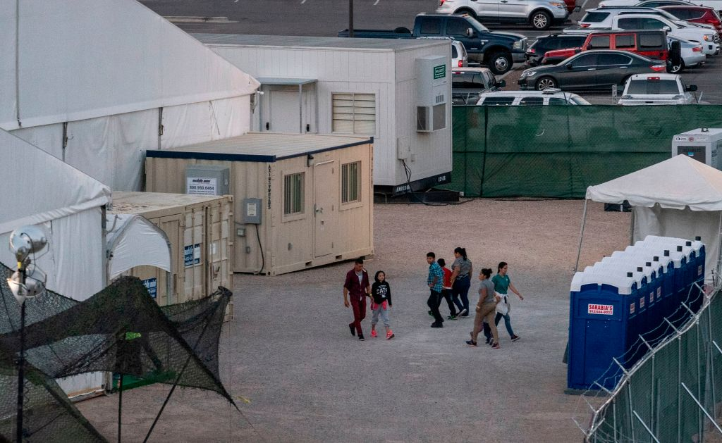 Immigrants are pictured behind the fences of a temporary facility set up to hold them at the El Paso Border Patrol Station, on June 21, 2019.