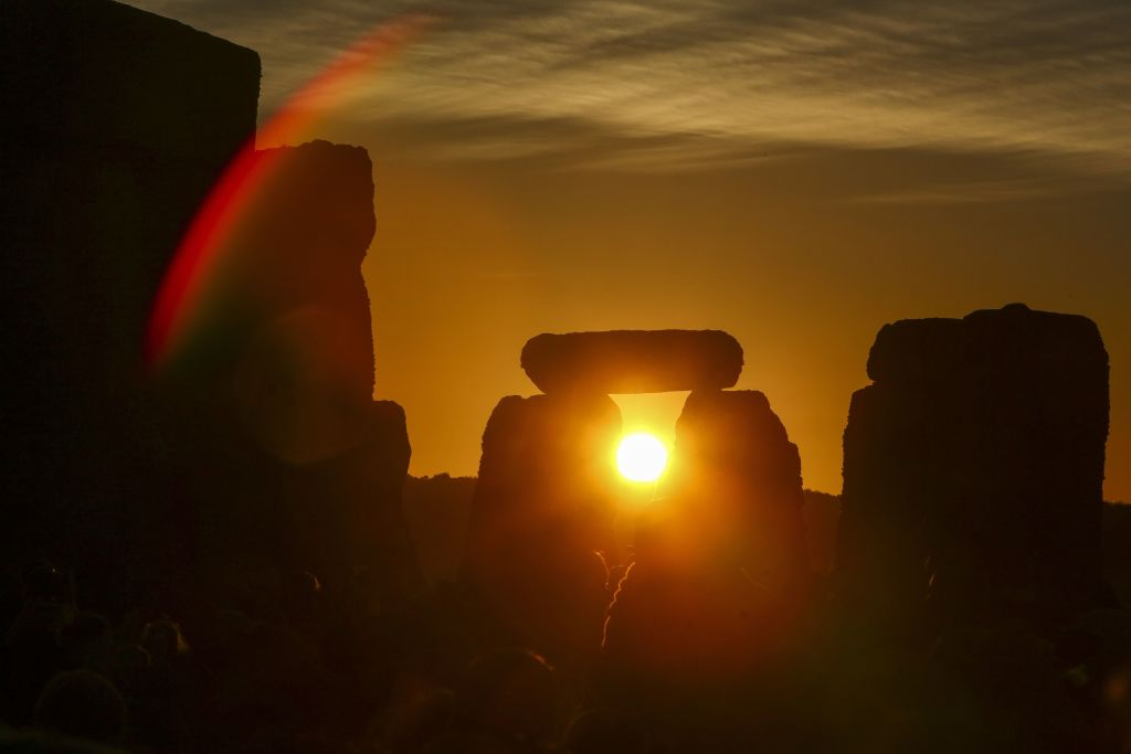 Revelers watch the sunrise as they celebrate the summer solstice at Stonehenge in Wiltshire, England on June 21, 2018.