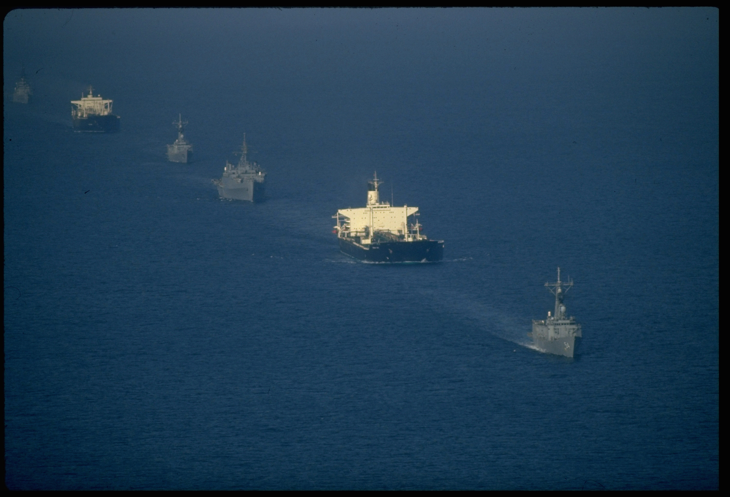 A convoy of US warships escorted re-flagged Kuwaiti oil tankers through Iran-Iraq tanker war plagued waters of Persian Gulf in 1987
