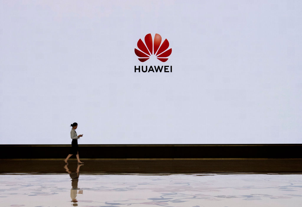 A member of Huawei's staff walks in front of a large screen displaying the logo in the foyer of a building used for high profile customer visits and displays at the company's Bantian campus on April 12, 2019 in Shenzhen, China.