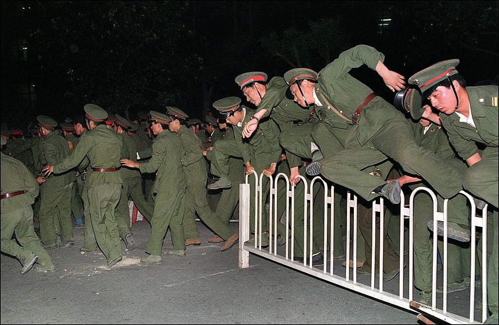 People's Liberation Army (PLA) soldiers leap over a barrier on Tiananmen Square in central Beijing June 4, 1989.