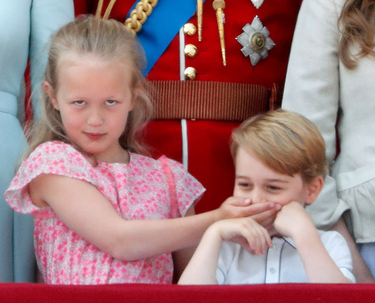 Savannah Phillips puts her hand over Prince George of Cambridge's mouth as they stand on the balcony of Buckingham Palace during Trooping The Colour 2018 on June 9, 2018 in London, England.