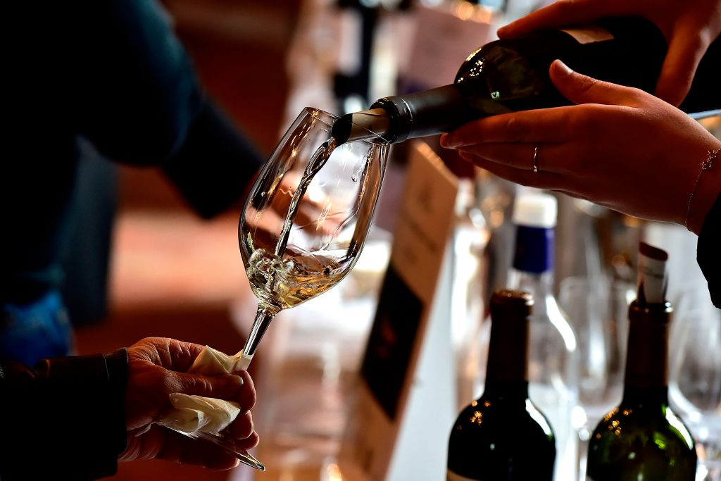 A woman serves white wine at a wine tasting session at the Chateau Carbonnieux in Cadaujac, near Bordeaux, southwestern France, on April 2, 2019, during the official 'Semaine des Primeurs' to present wines from the Bordeaux region. President Trump is complaining about France charging high tariffs on U.S. wine while they enter the U.S. virtually tariff-free.