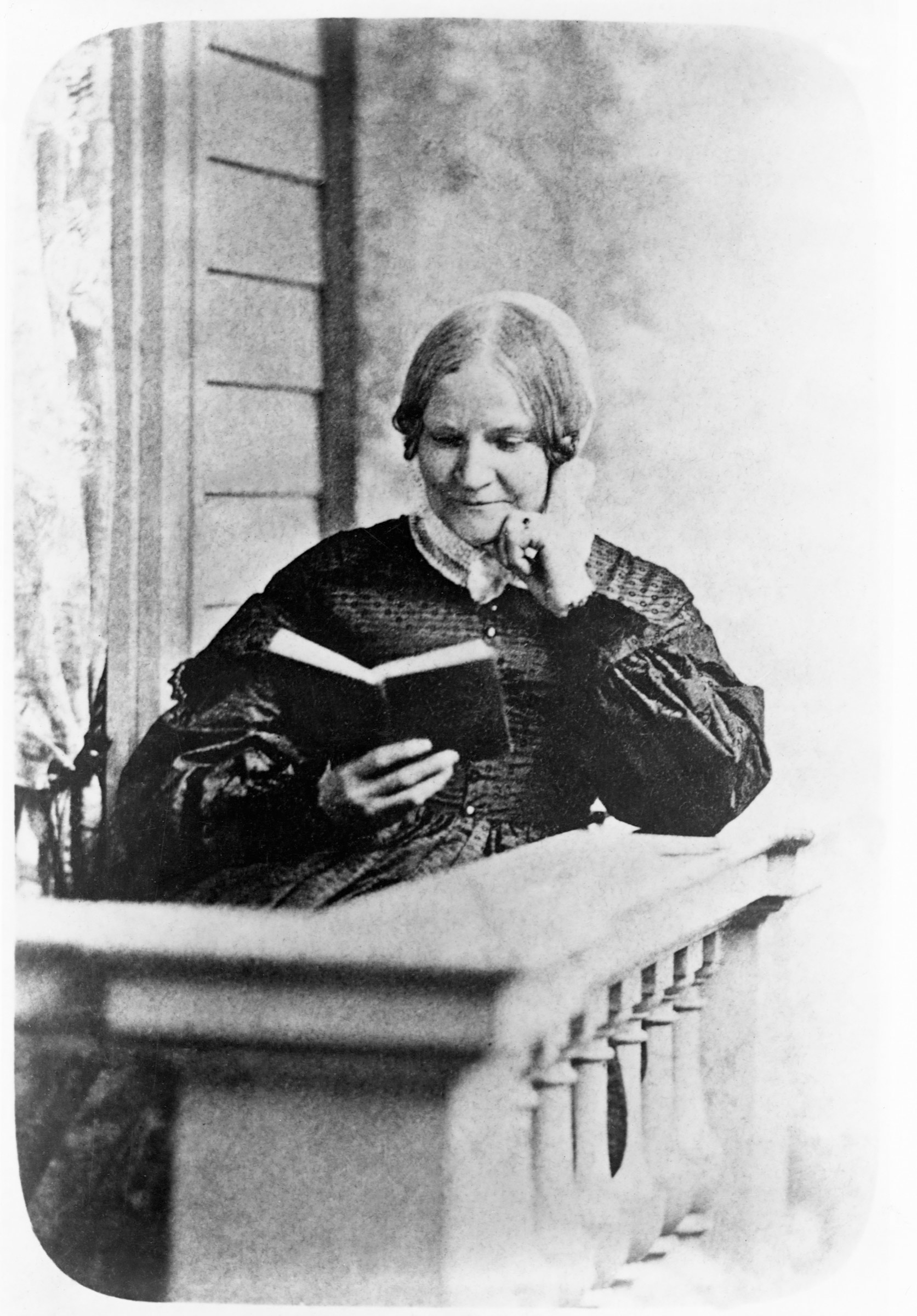 Lydia Maria Child (1802-1880) reads a book on a front porch. Child wrote and edited books promoting the suffragist and abolitionist causes.