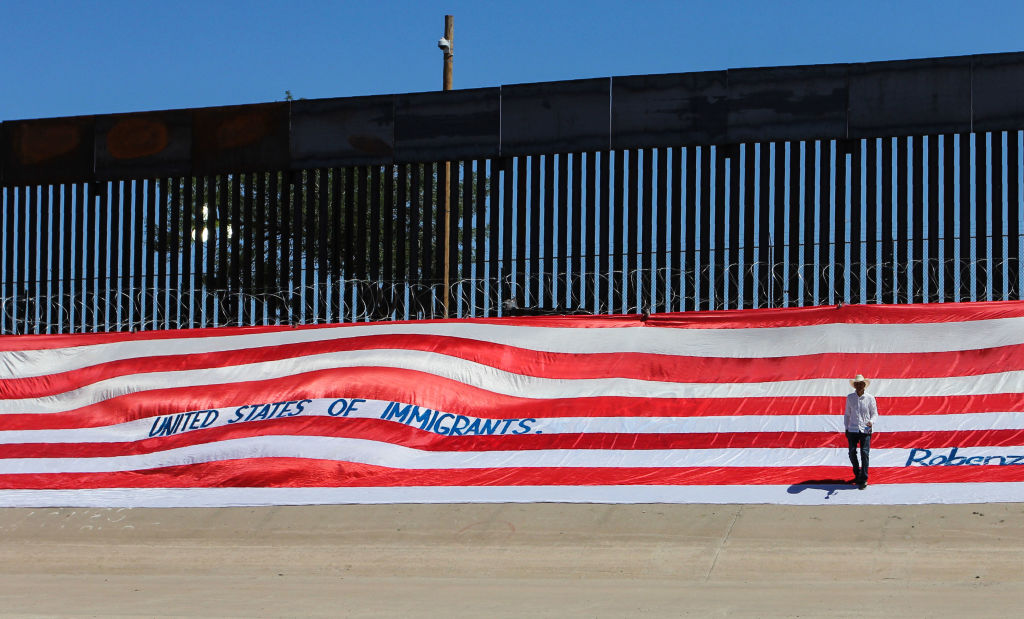Mexican U.S. resident Roberto Márquez, places a United States national flag on the border wall next to Rio Grande river to demonstrate against the immigration policies of Donald Trump in the border between El Paso, US, and Ciudad Juarez, Mexico, on June 6, 2019.