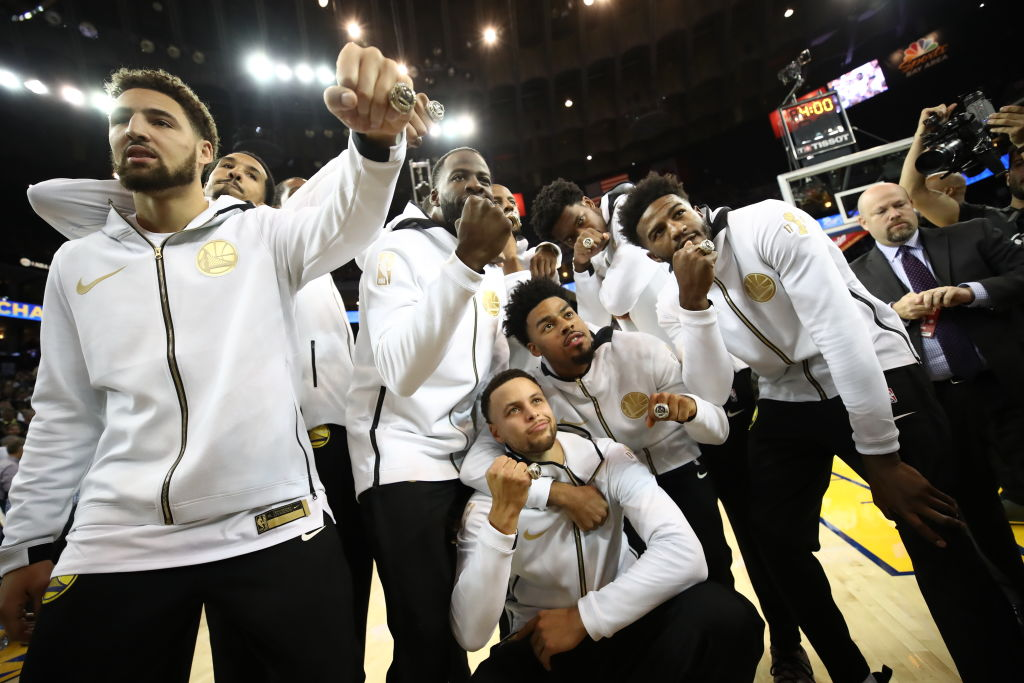 Stephen Curry #30 and the Golden State Warriors celebrate after receiving their 2017-2018 Championship rings prior to their game against the Oklahoma City Thunder at ORACLE Arena on October 16, 2018 in Oakland, California.