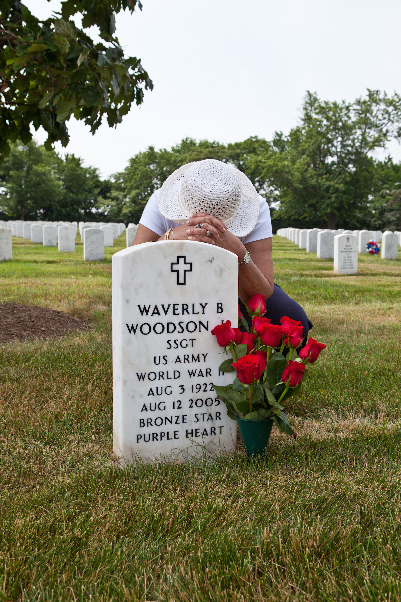 Joann Woodson visits her husband's grave at Arlington National Cemetery with his favorite red roses.