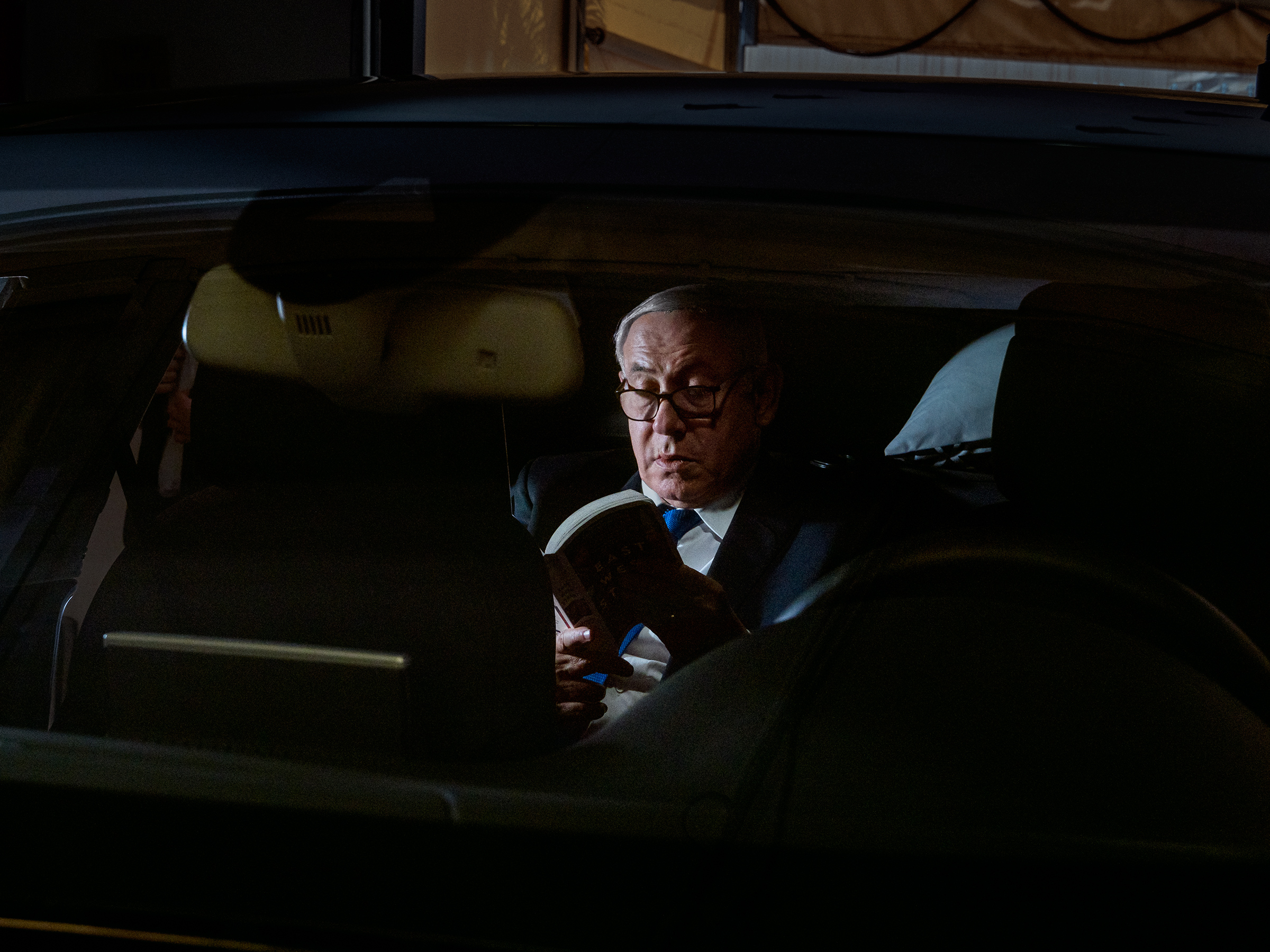 Netanyahu reads inside his car in Jerusalem on June 25.