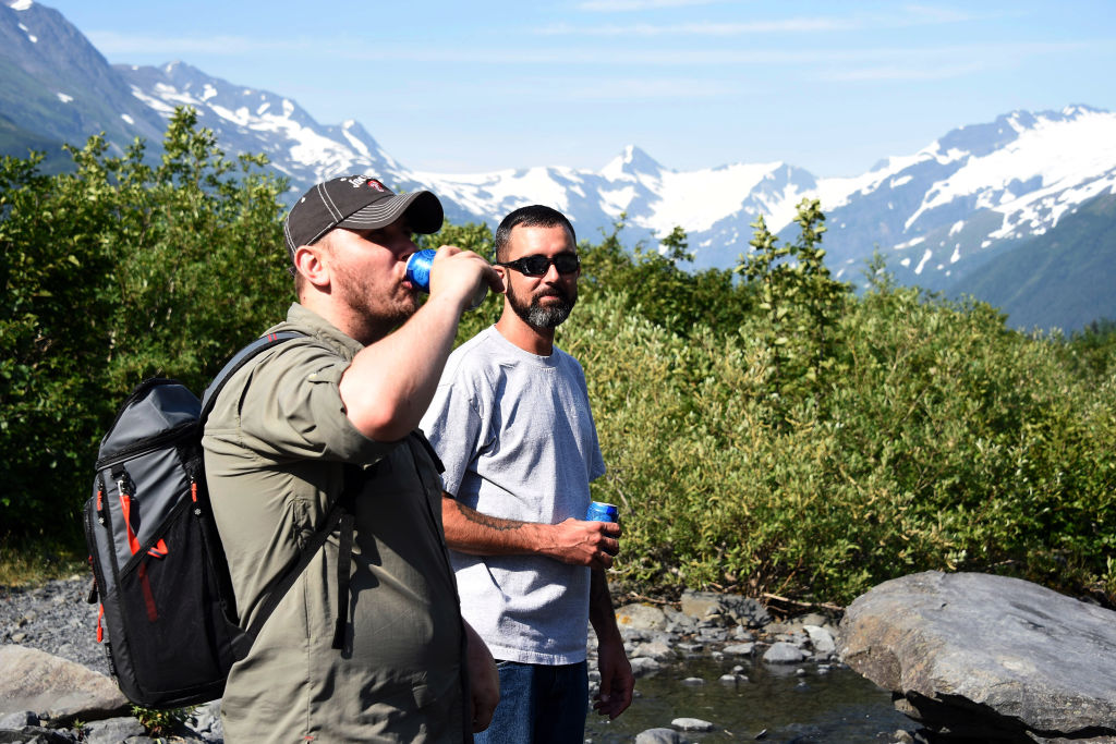 Sam Lightle, left, from Anchorage, and Brandon York from Jacksonville, Florida, take in the scenery along a creek below the Byron Glacier on July 4, 2019 near Portage Lake in Girdwood, Alaska. Alaska is bracing for record warm temperatures and dry conditions in parts of the state.