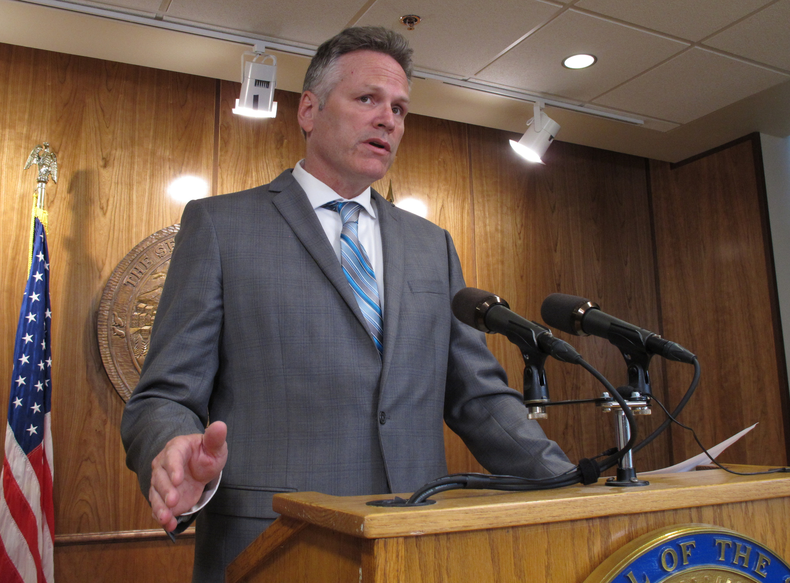 Alaska Gov. Mike Dunleavy speaks to reporters about his budget vetoes at the state Capitol in Juneau, Alaska Friday, June 28, 2019. The university system, health and social service programs and public broadcasting were among the areas affected by vetoes. The budget agreed to by the House and Senate cut state support for the university system by a fraction of what Dunleavy proposed. Lawmakers have the ability to override budget vetoes if they can muster sufficient support.