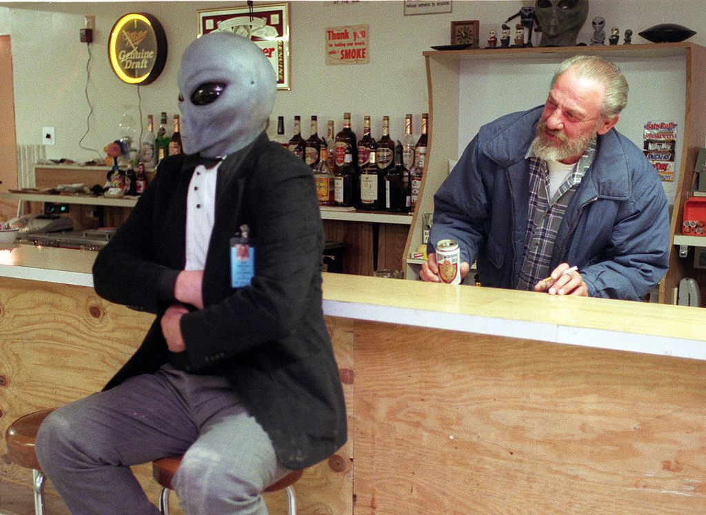 Photo of Pat Bailey of San Francisco December 04, 1995, who was attending a UFO convention earlier in the day, came into the Little A'Le'Inn located in Rachel, Nevada, near the Nellis Air Force Base and Area 51, wearing an alien mask. Looking on is bar owner Joe Travis, who believe it or not seemed a bit surprised.
