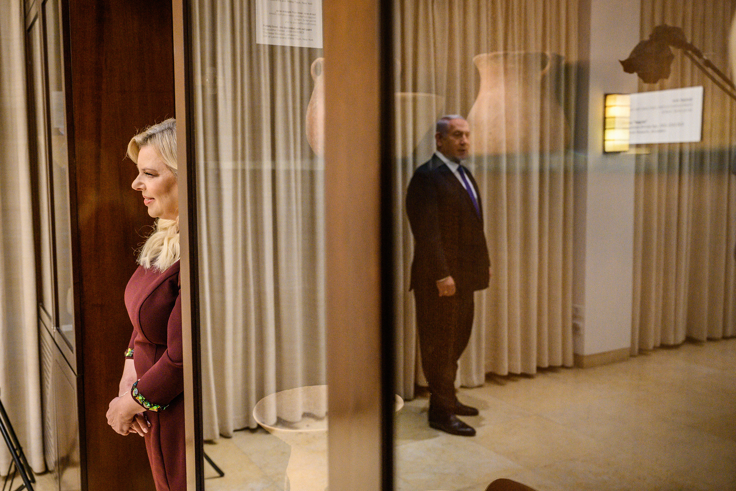 Sara Netanyahu looks on as the Prime Minister stands for a portrait in their residence in Jerusalem.