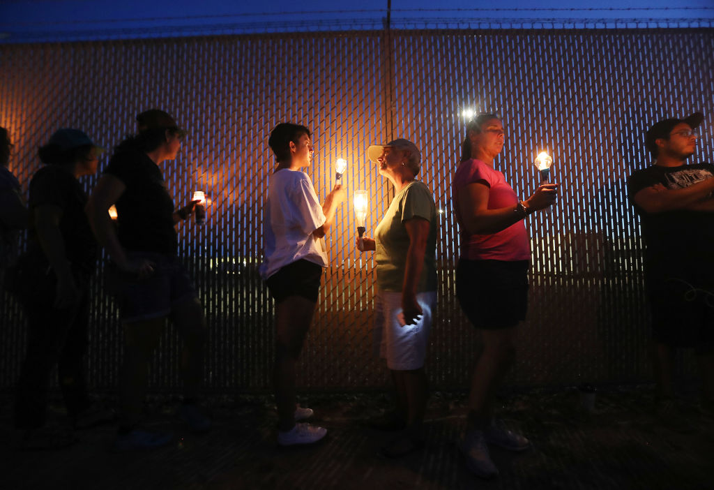Activists hold a candlelight vigil at the perimeter fence securing the U.S. Border Patrol station where lawyers reported that detained migrant children were held unbathed and hungry on June 25, 2019 in Clint, Texas.