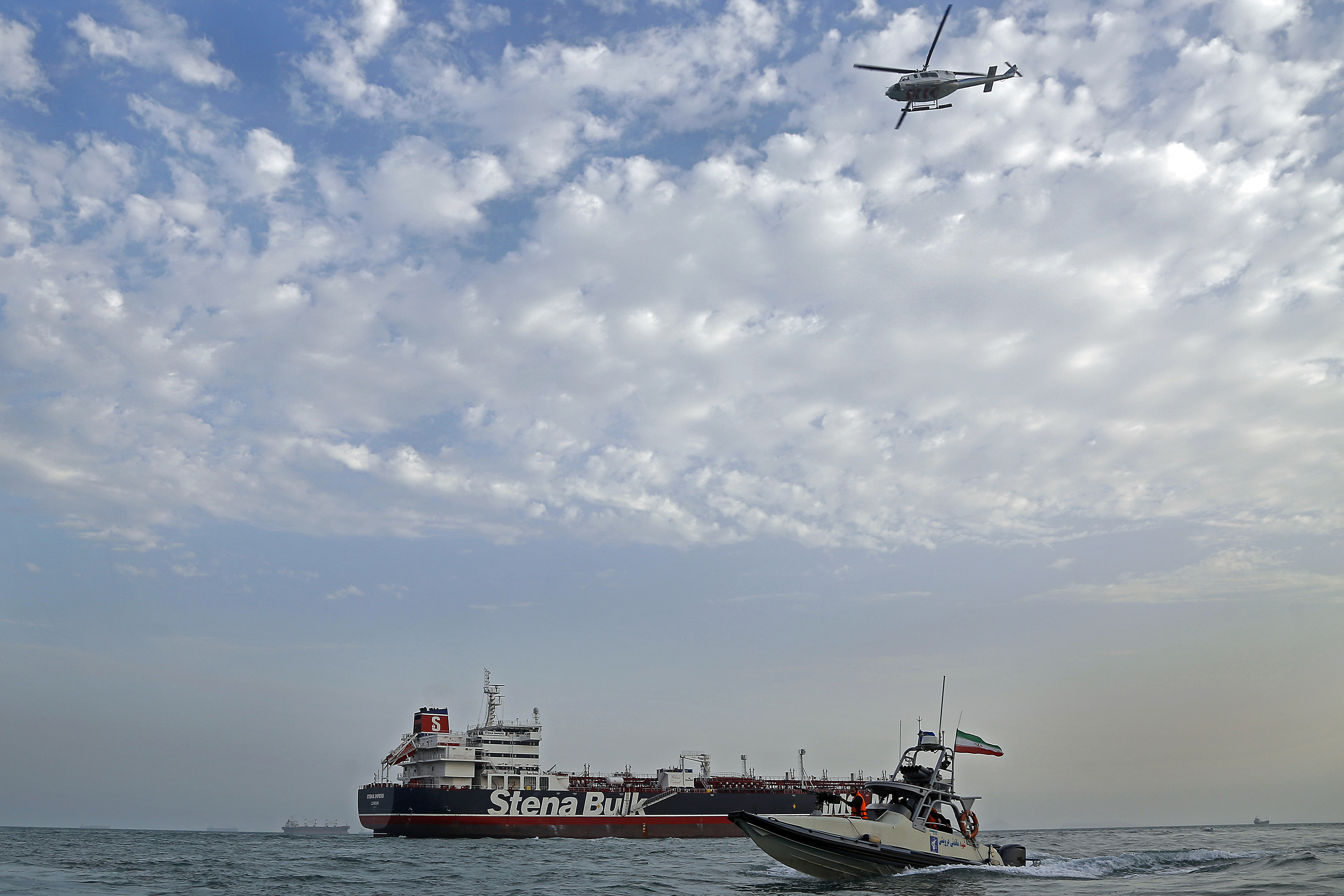 A speedboat and a helicopter of Iran's Revolutionary Guard move around a British-flagged oil tanker MV Stena Impero on July 21, 2019, after it was seized by Iran in the Persian Gulf