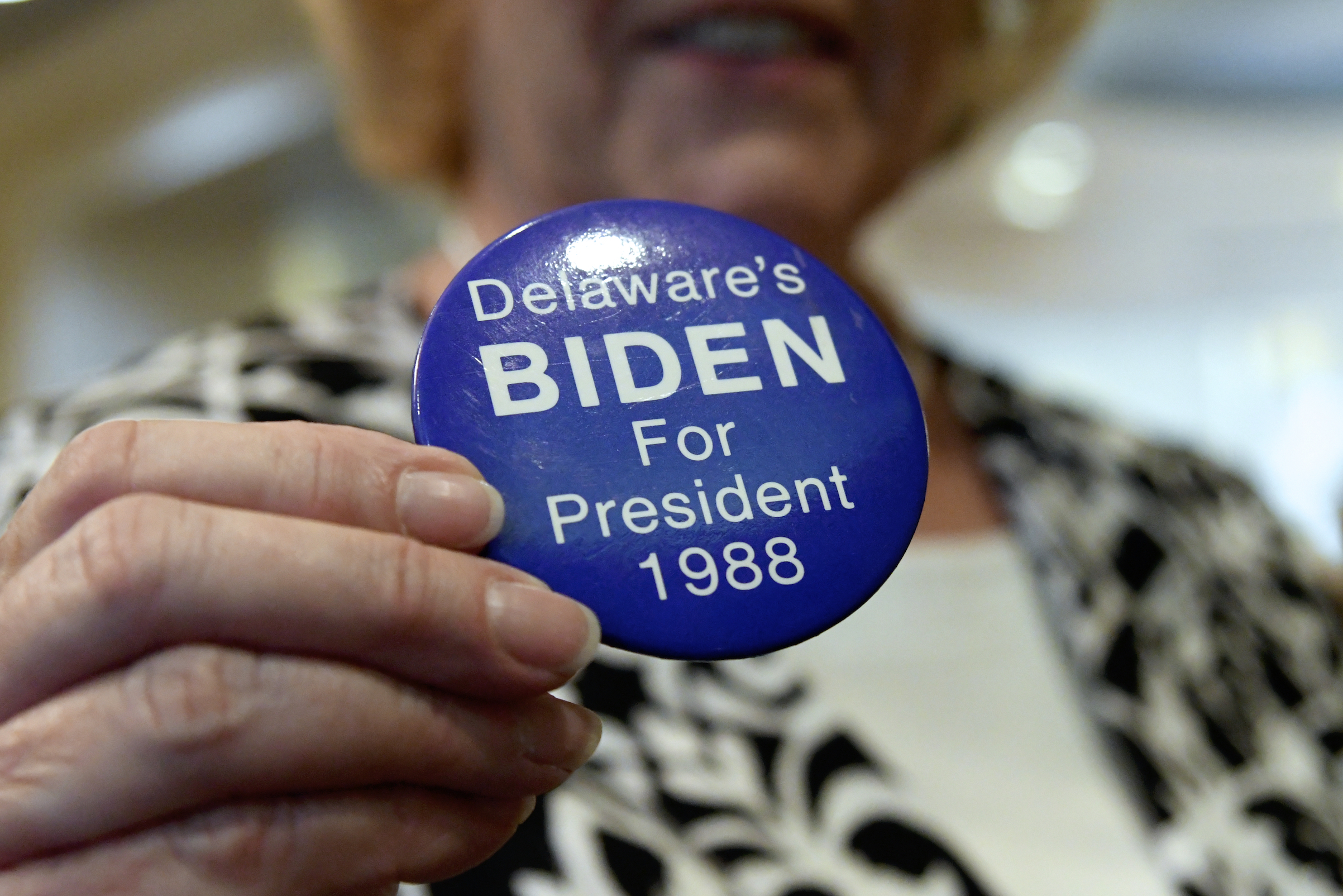 A supporter holds up a Biden for President button from 1988 in Dover, Del., on March 16, 2019.