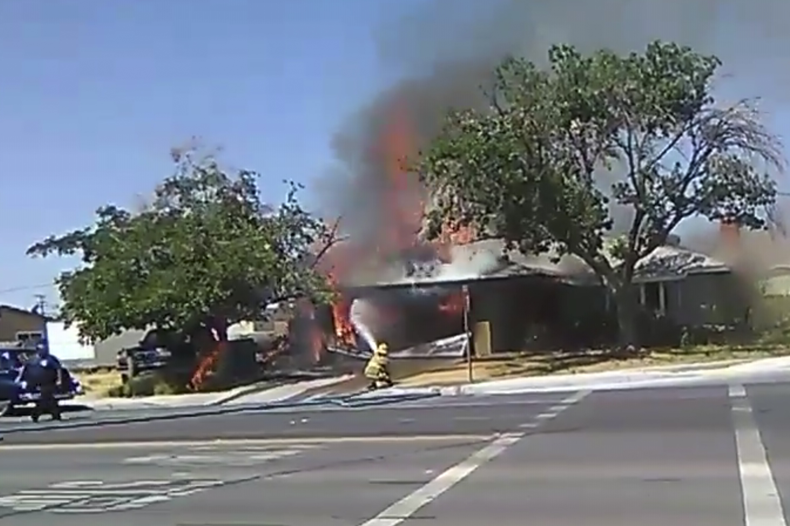 In this image taken from video provided by Ben Hood, a firefighter works to extinguish a fire, Thursday, July 4, 2019, following an earthquake in Ridgecrest, Calif.
