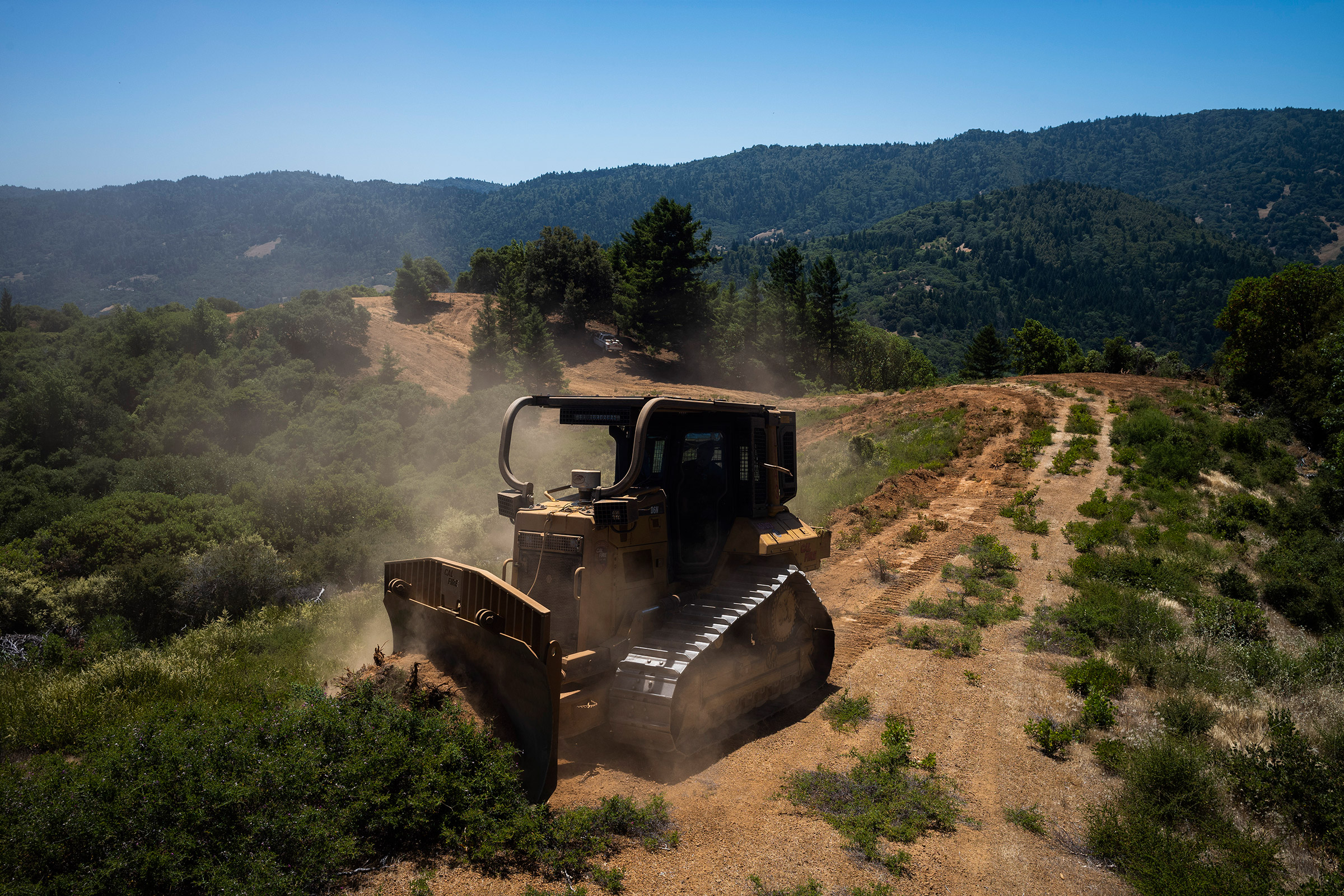 A bulldozer works on a firebreak, a gap in vegetation that acts as a barrier to slow the progress of a wildfire, in the hills surrounding Ukiah.