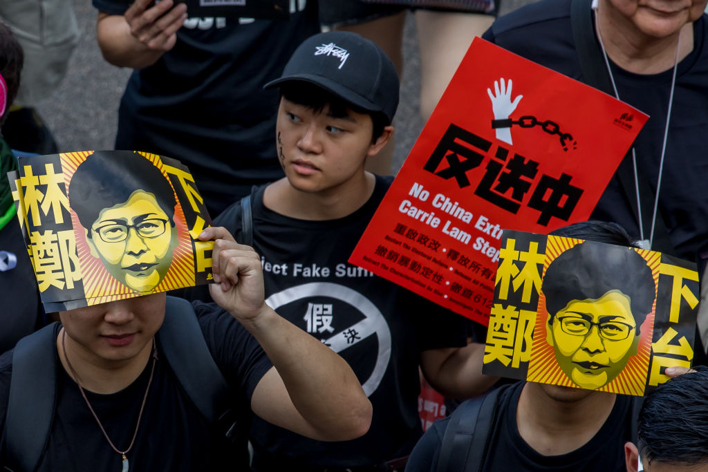 Protesters carry placards calling for Hong Kong Chief Executive Carrie Lam to step down during a rally in Hong Kong on July 1, 2019.