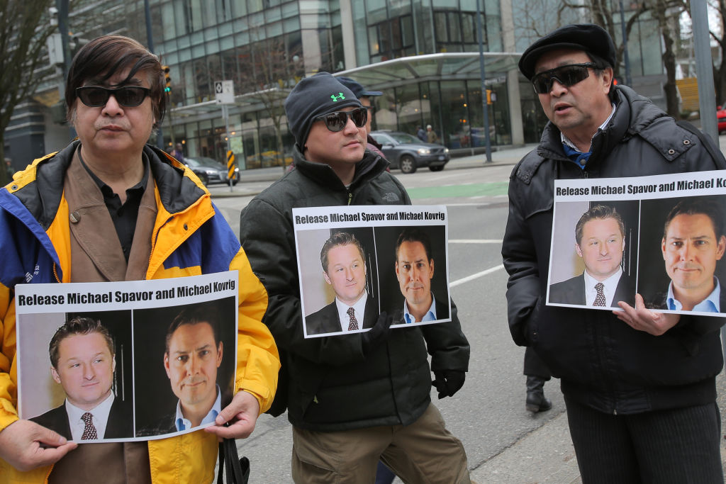 Protesters hold signs calling for the release of Canadian citizens outside British Columbia Superior Court in Vancouver, Canada on March 6, 2019.