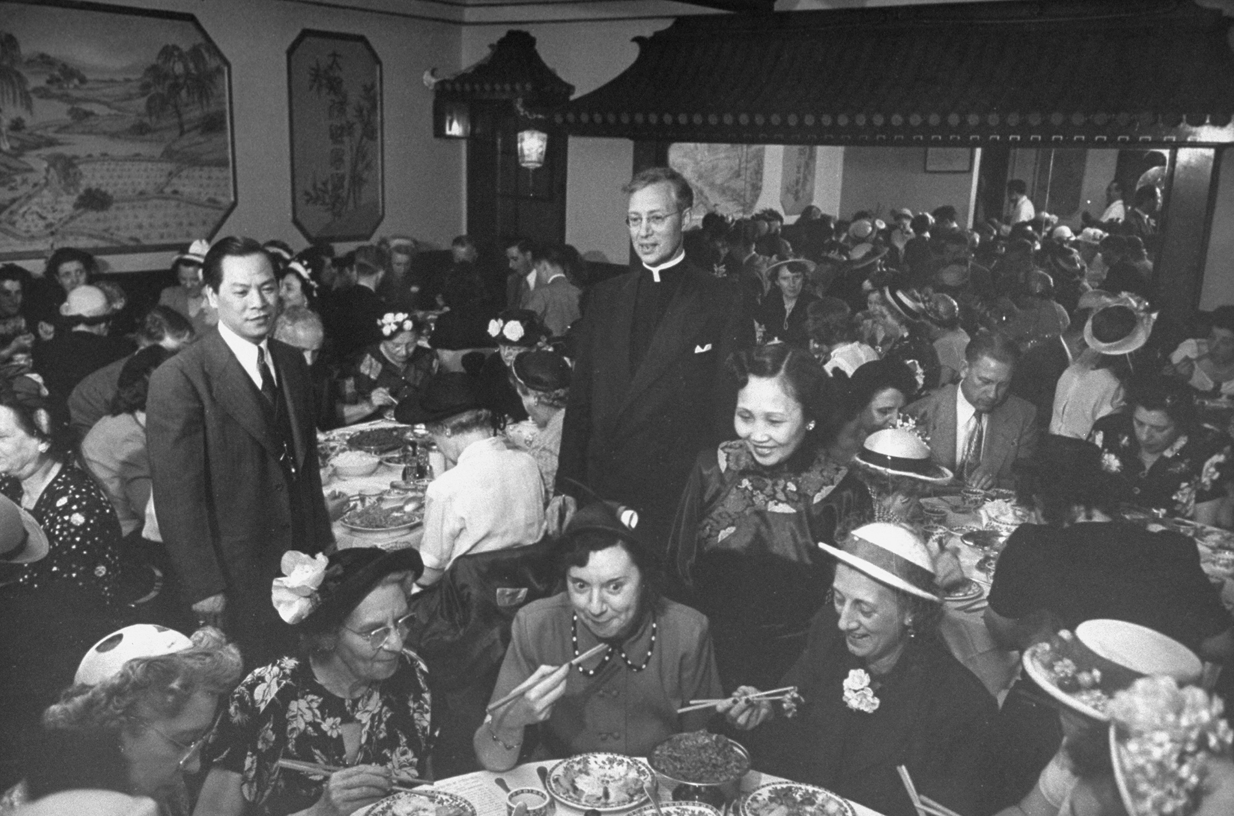 Chin Dut Toy (L) standing in his restaurant, watching tourists try his Chinese food in December 1950 in New York City.