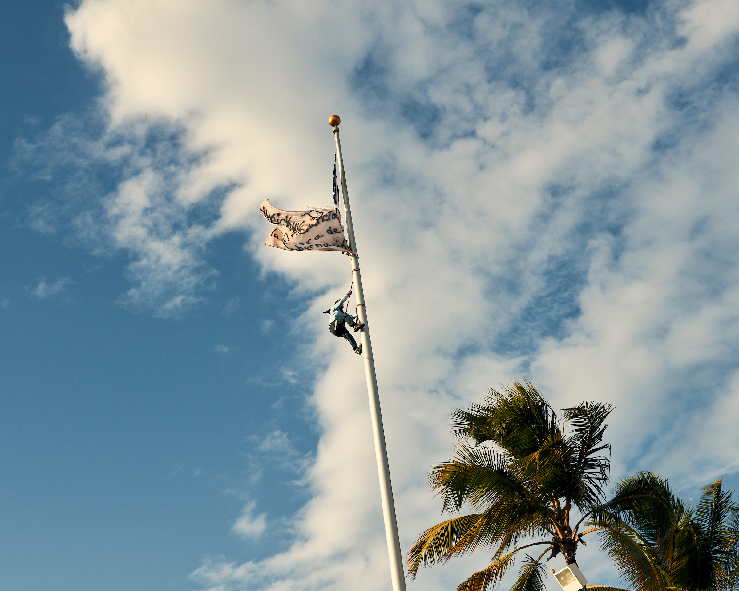 A protester scales a flag pole during a protest calling for Governor Ricardo Rosselló's resignation in the wake of  chatgate  in San Juan on July 17, 2019.