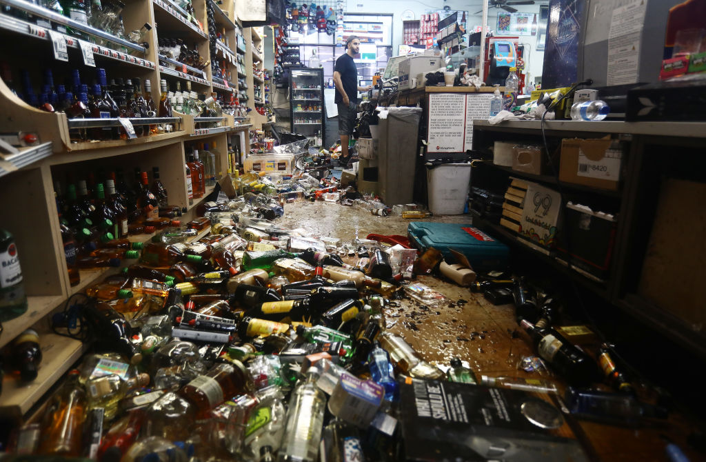 An employee stands at the register as broken bottles are scattered on the floor in Eastridge Market, following a 7.1 magnitude earthquake which struck nearby on July 6.