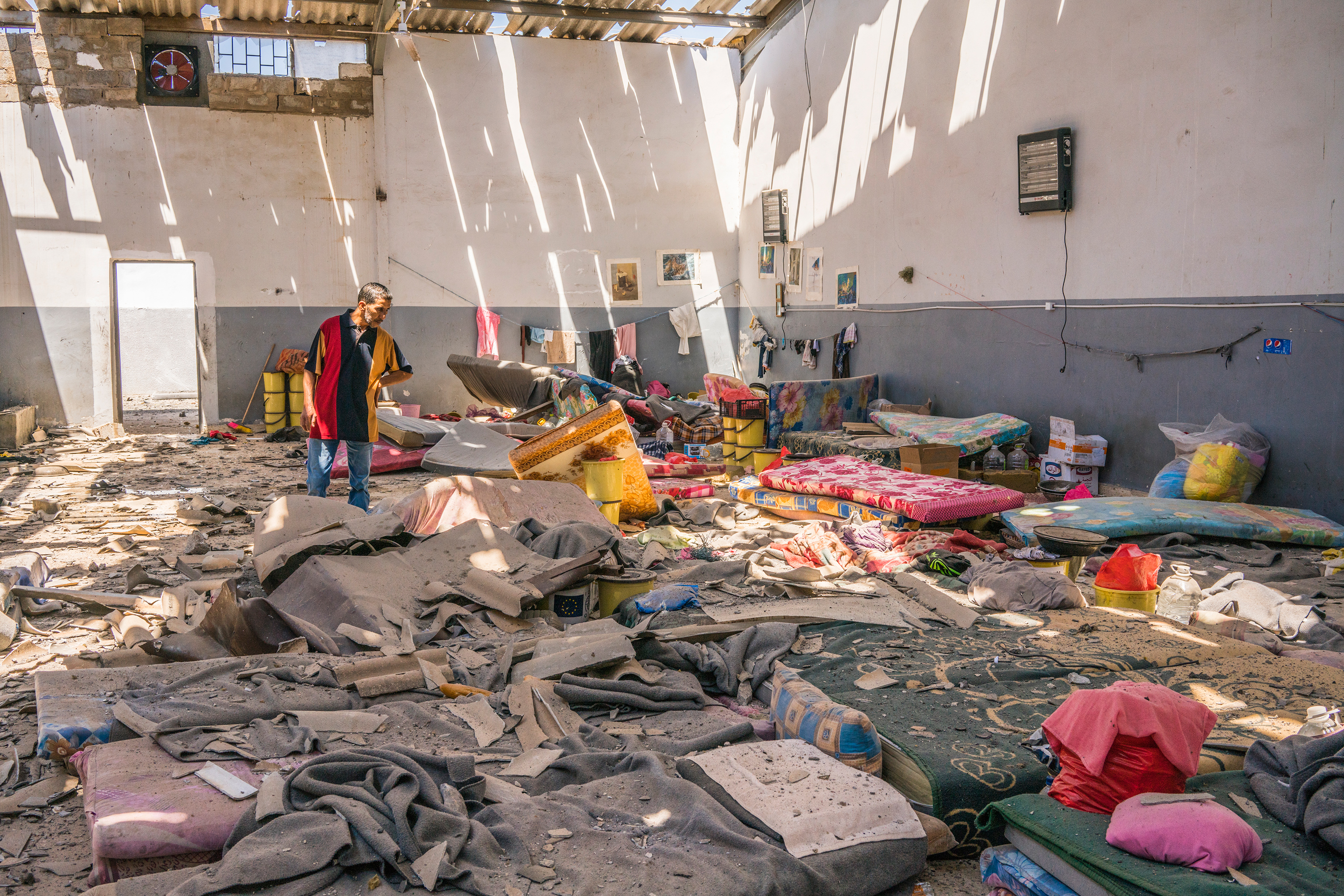 A man inspects damage to an area where migrants slept inside the Tajoura detention center near Tripoli, Libya, on July 3.