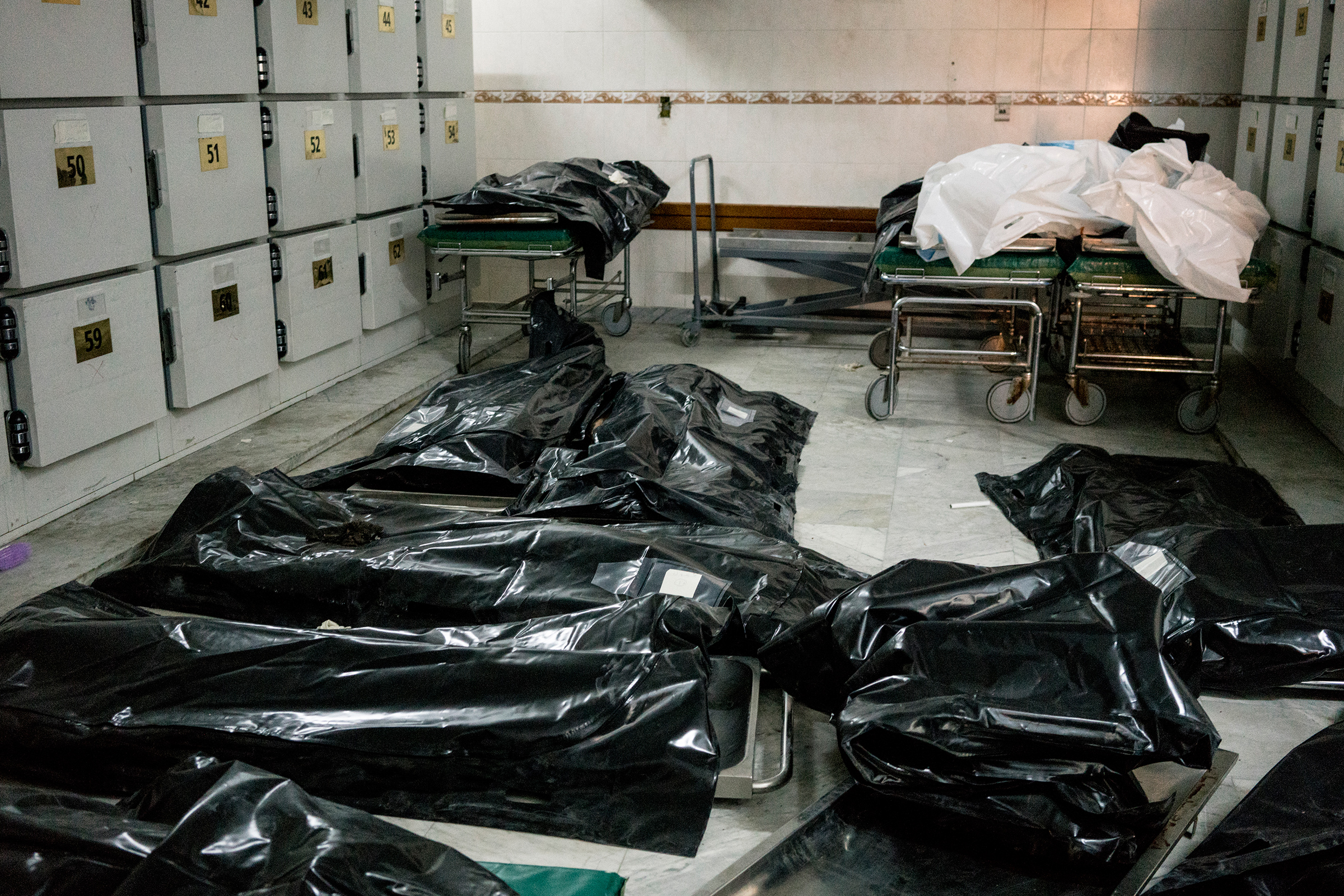 Bodies of migrants killed in the airstrike lay on the floor of the Tripoli Central Hospital morgue.