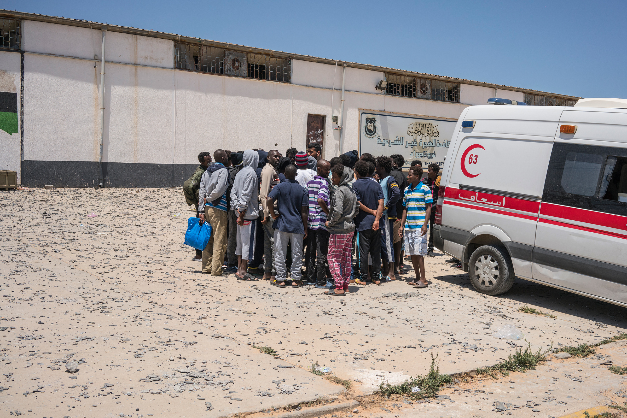 A group of migrants gather next to an ambulance outside the detention center.