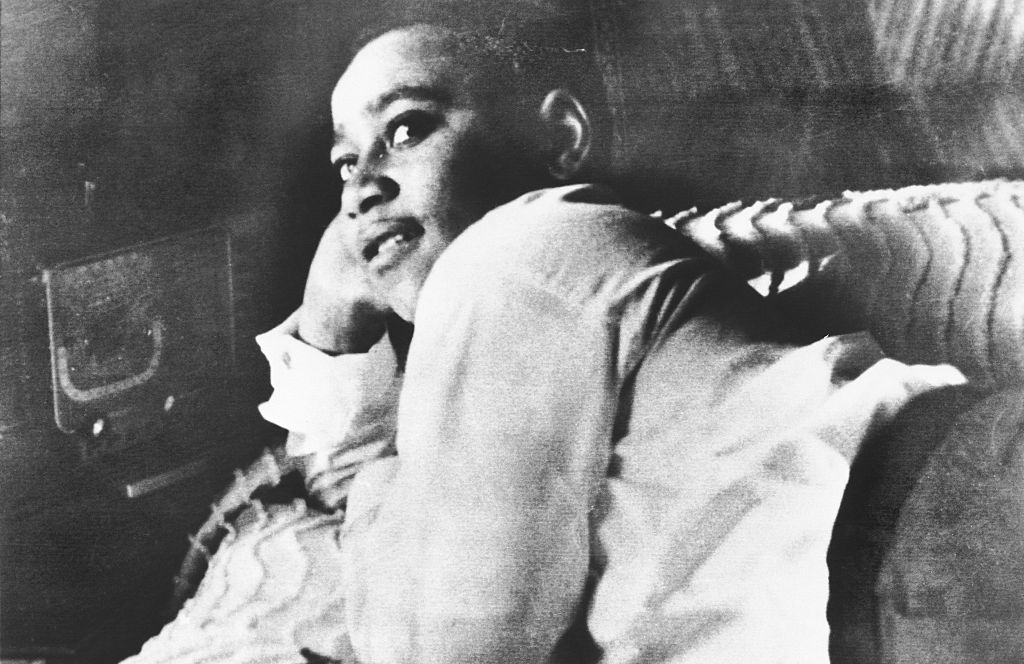 Emmett Till is shown lying on his bed.