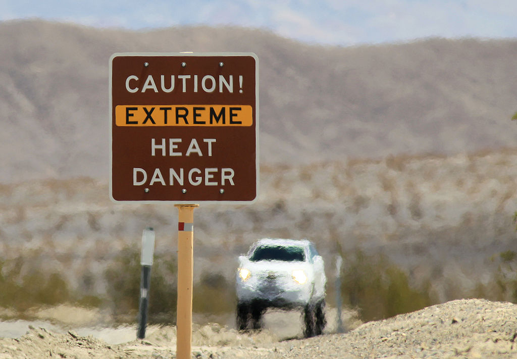 Heat waves rise near a heat danger warning sign on the eve in Death Valley National Park in California.