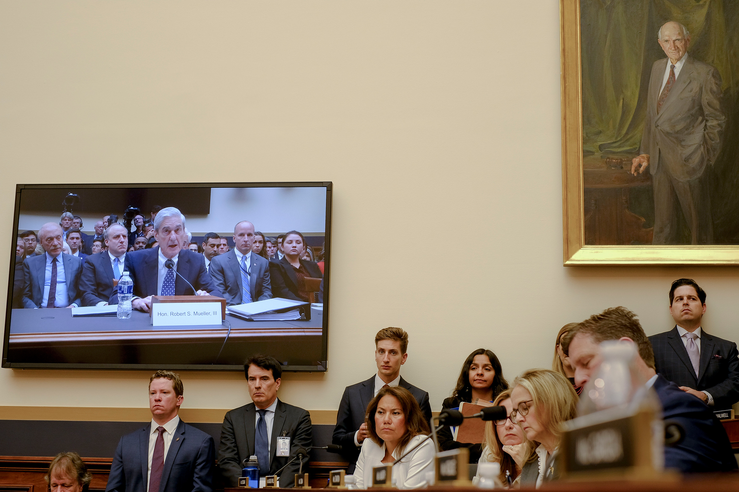 A television in the room broadcasts Mueller's testimony before the House Judiciary Committee.