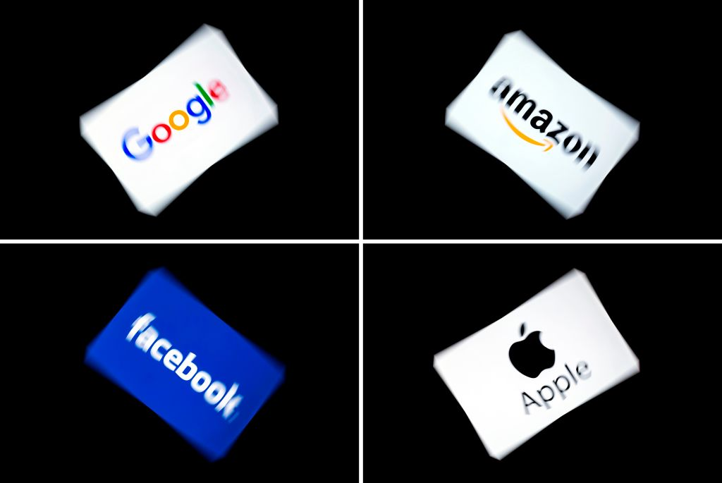 This combination of pictures shows the logos of the GAFA's, named after US  multinational technology and Internet-related services company Google, US online retail giant Amazon, US social media Facebook and US multinational technology company Apple, displayed on a tablet in Paris, on February 18, 2019.